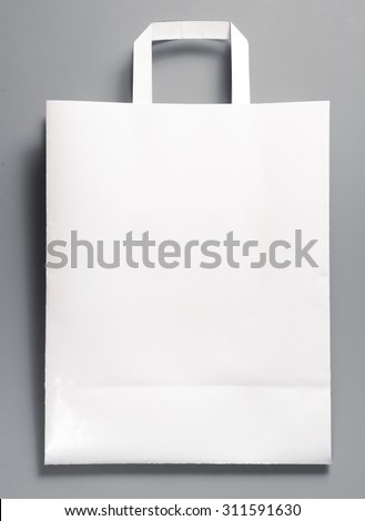 White paper bag with handles on gray background - stock photo