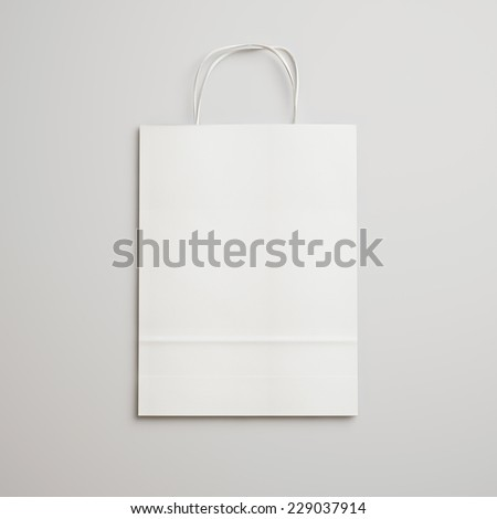 White paper bag with handles on light gray background - stock photo