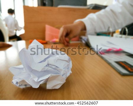 White paper ball on a wooden table with blurred background in office.copy space