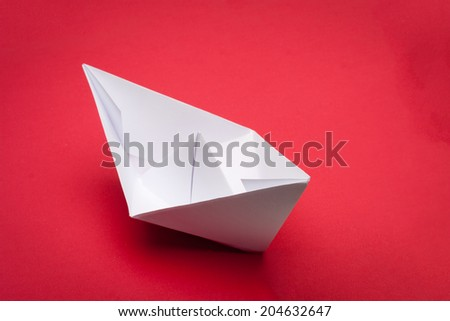 white paper boat on red paper background