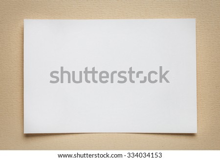 white paper card on beige background, place for text