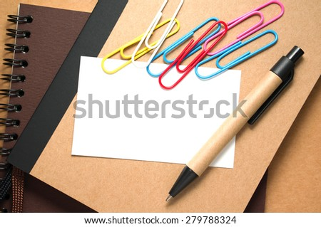 White paper card on notebook with pen on kraft cardboard background - stock photo