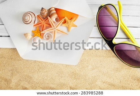 White paper envelope full of seashells and sunglasses on a wooden planks over sandy background. - stock photo