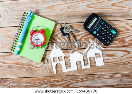 White paper house figure with keys, notebook, red alarm clock and calculator on wooden background. Real Estate Concept.