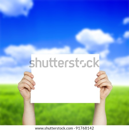 white paper in hand and green field with blue sky