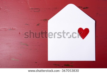 White paper love letter envelope with red heart on red background on red wood table background, with copy space for your text here.  - stock photo