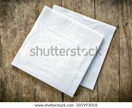 white paper napkins on old wooden table - stock photo