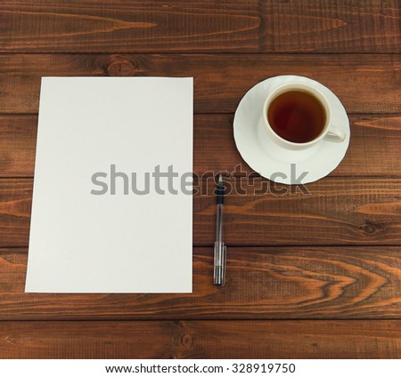 White paper on a wooden table next to a cup of tea, and ballpoint pen - Business concept with space for Your text and picture