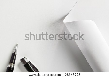 White paper, partially rolled up, and pen - stock photo