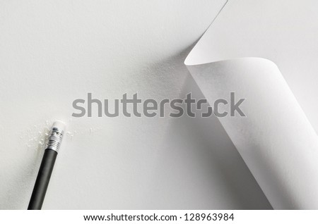 White paper, partially rolled up, with pencil and rubber - stock photo