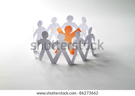 White paper people standing in a cycle and one orange paper man inside. Isolated on white background