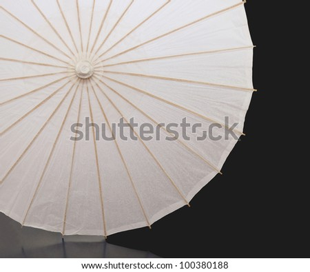 White paper umbrella with wood splines on black background - stock photo