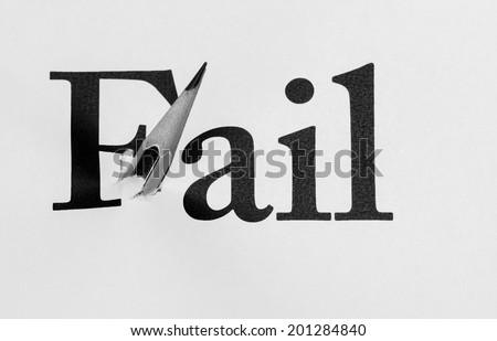 """white paper was punching  by the pencil at the word """"fail"""" on black and white color - stock photo"""