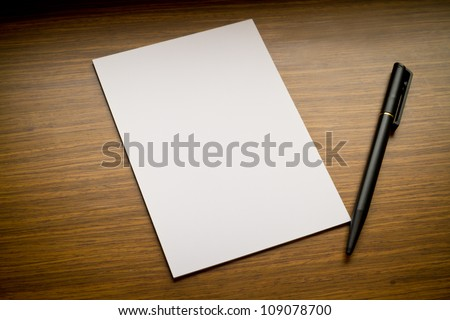 white paper with black pen on wooden table - stock photo