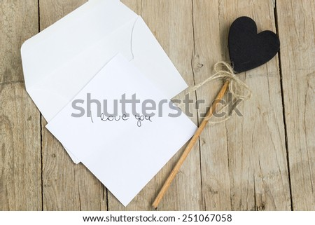 White paper with I love you sign with heart-shaped decoration and an envelope on a wooden table. - stock photo