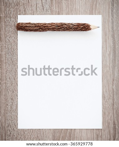 White paper with wooden pencil on wood table background - stock photo
