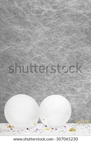 White party balloons, party decorations and confetti on a white table cloth - stock photo
