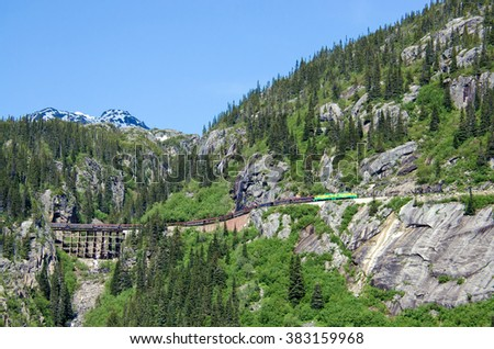 White Pass & Yukon Route Railroad travels along the cliffs after exiting Tunnel Mountain - stock photo