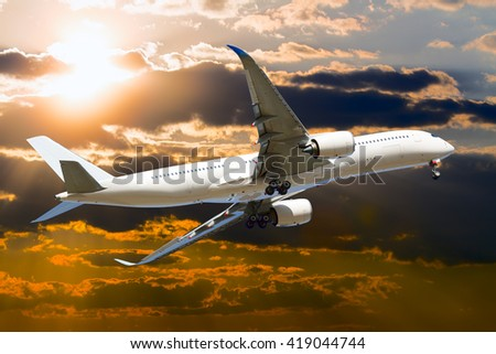 White passenger airplane is flies against the backdrop of cloudy sunset sky