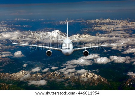 White passenger airplane is flying in the blue sky over the clouds and mountains - stock photo