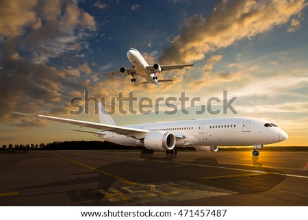 White passenger airplane on airport runway during sunset. And aircraft in the sky.