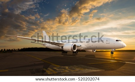 White passenger airplane on the airport runway. The plane is taking off during a colorful sunset.
