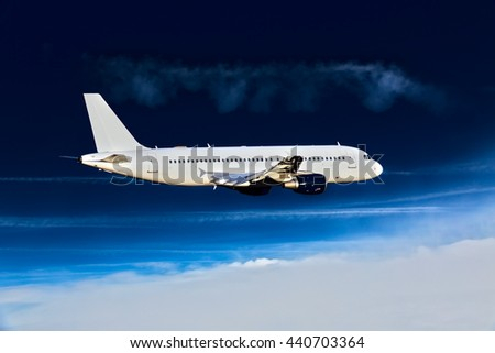 White passenger airplane with blue engines. Aircraft is flying high in the deep-blue sky. - stock photo