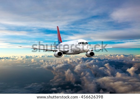 White passenger airplane with red and blue Tail. Aircraft is flying in the blue cloudy sunset sky. - stock photo