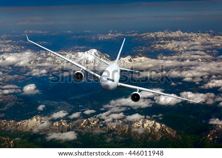 White passenger airplane with right roll. Aircraft is flying in the blue sky over the clouds and mountains. - stock photo