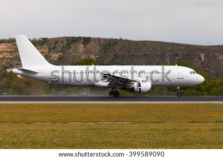 White passenger plane a few seconds after landing. The aircraft moves along the runway. - stock photo