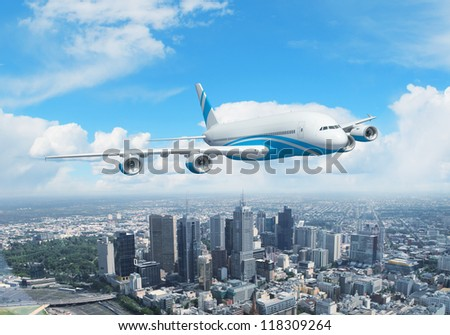 White passenger plane flying in the day blue sky above a city - stock photo