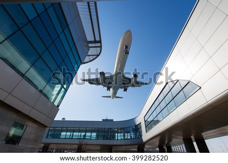 White passenger plane in blue sky. Aircraft is flying low over the Airport Terminal. - stock photo
