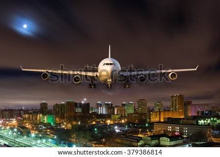 White passenger plane in moonlight. Aircraft is flying over the night city.