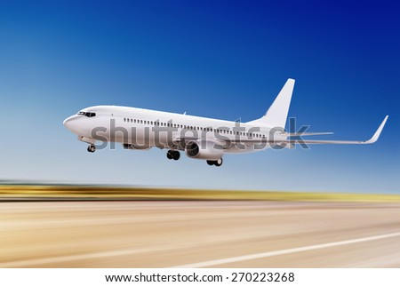 white passenger plane is flying up from airport  - stock photo