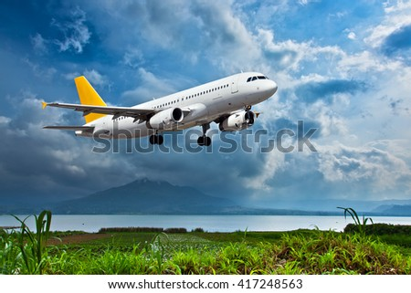 White passenger plane with yellow Tail is climbing in the cloudy sky. Aircraft flies over green grass and lake with mountain at the background.