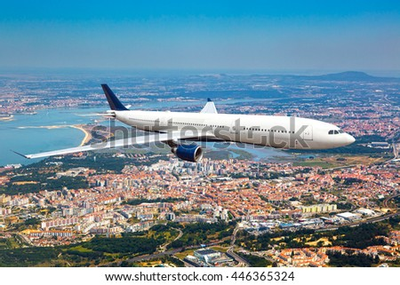 White passenger wide-body airplane. Aircraft is flying in the blue sky over the city rooftops and river. - stock photo