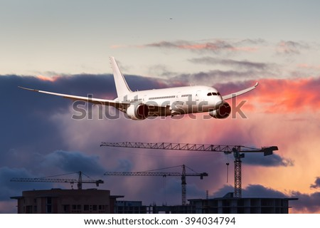 White passenger wide-body plane. Aircraft is flying over the construction cranes with sunset sky at background. - stock photo