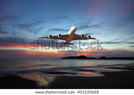 White passenger wide-body plane in sunset colors. Aircraft is flying over the sea and beach. - stock photo
