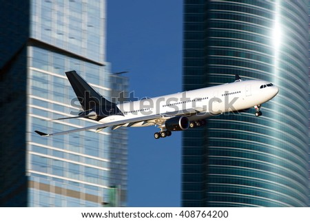 White passenger wide-body plane with a black tail and black engines. Aircraft flies against the backdrop of skyscrapers and clear blue sky. - stock photo