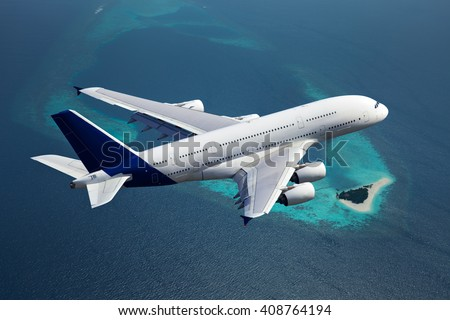 White passenger wide-body plane with blue tail. Aircraft is flying over the deep-blue ocean and island. - stock photo