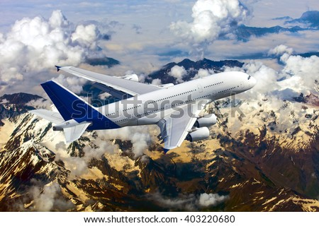 White passenger wide-body plane with blue tail. Aircraft is flying over the high mountains. - stock photo