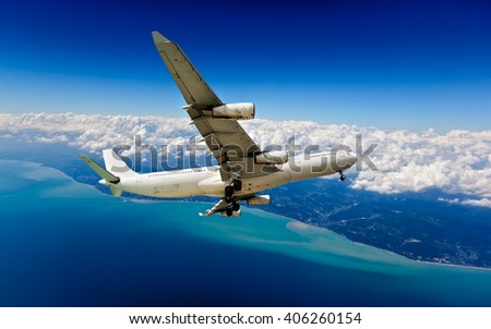 White passenger wide-body plane with 4 (four) Engines. Aircraft is flying in the cloudy sky, over the deep-blue ocean. - stock photo
