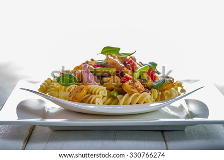 White pasta plate with vegetables and sausage on white background