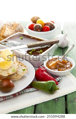 White pate dish with knife, bread, butter, chutney, tomatoes, peppers and garlic on red checkered cloth over green painted grunge style wooden table - stock photo