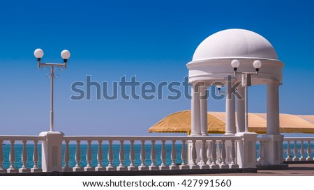 White pavilion at seashore under blue sky - stock photo