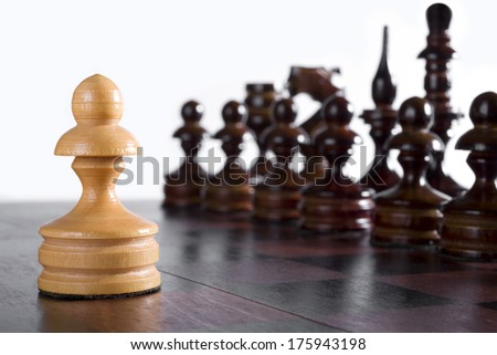 White pawn against black chess pieces formation. Opening gambit - stock photo