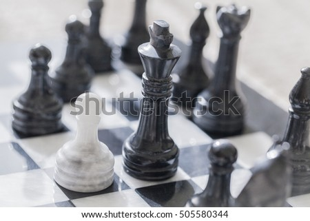 White pawn on a chess board alone against all black pieces. White pawn fight against black enemy team on board.