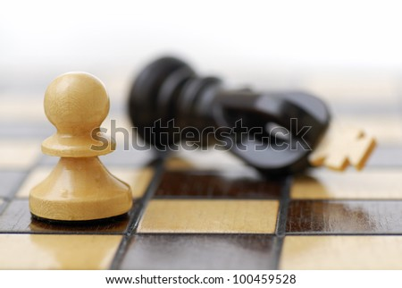 White Pawn standing over defeated black King. Class Struggle. - stock photo