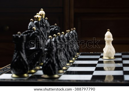 white pawn surrounded by black chess pieces on a chess board home - stock photo