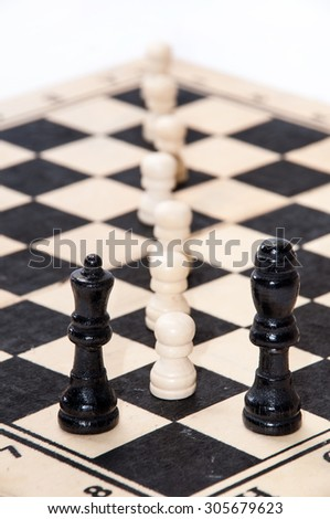 White pawns in front of a black queen and king.